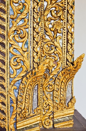 Golden carving on the door of Thai church.  photo