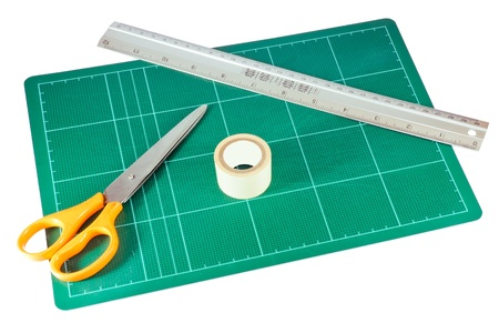 Orange scissors and metal ruler on the green cutting pad. photo