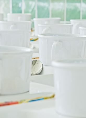 White coffee cup  arranged in a row in front of the meeting rooms. photo