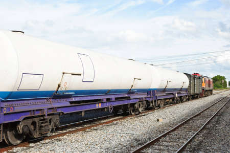 Bogie gas tanker in freight train on station.  photo