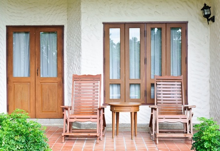 front or back yard: Wooden rocking chair on the paito of house.