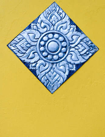 Silver carvings in Thai style on the yellow wall. photo