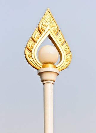 Golden lantern poles with traditional Thai sculpture in the park  photo