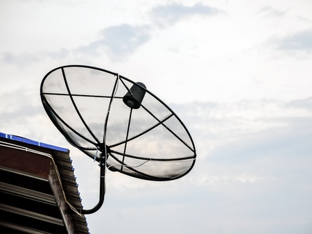 Single satellite dish on the roof of old house Stock Photo - 13672878