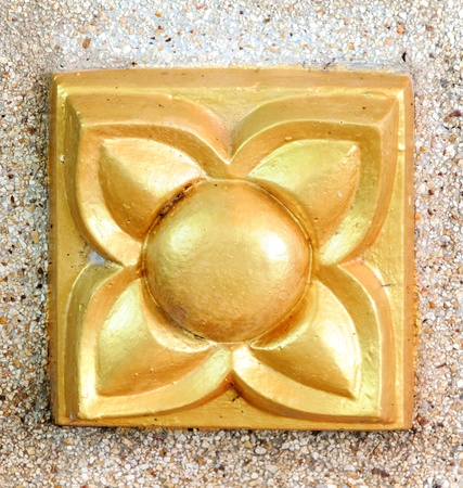 Golden flower statue on the temple wall. photo