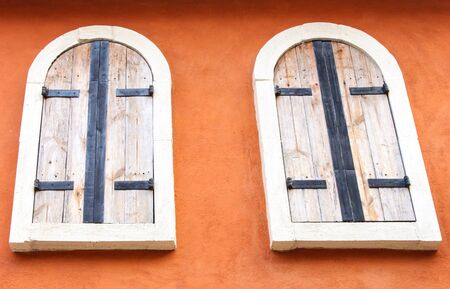 twin house: Twin wooden window on the orange wall of country house.