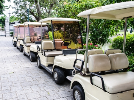 White golf cart is park near the entrance of palace
