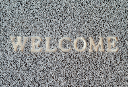 welcom: Dirty welcom doormat  placed near the entrance  Stock Photo