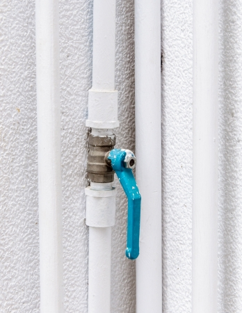 Blue faucet in the white pipe of factory wall Stock Photo - 17245753