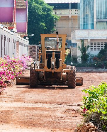 Motor grader in the temple for construc the car park  photo