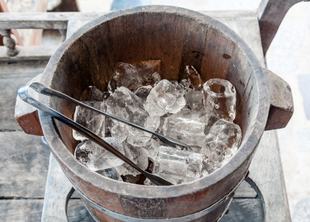 tong: Ice wooden bucket on the table of Thai restaurant