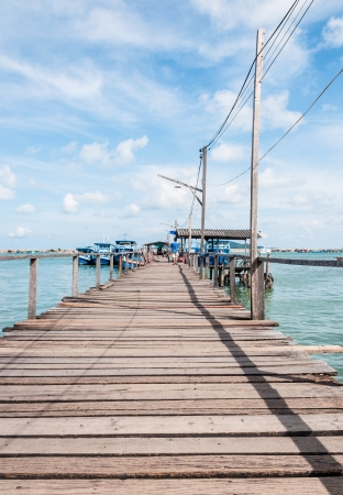 Wooden pier to the travel boat in the summer sky  photo