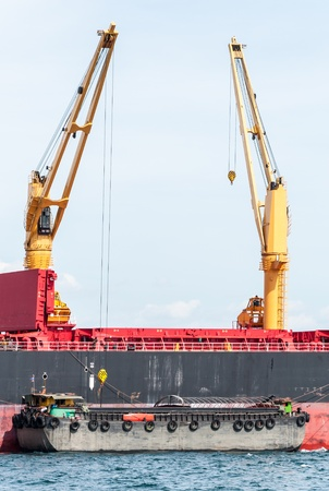 Modern carn in the large cargo ship is lifting the goods from small ship  photo