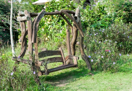 Old wooden swing in the garden of country house Stock Photo