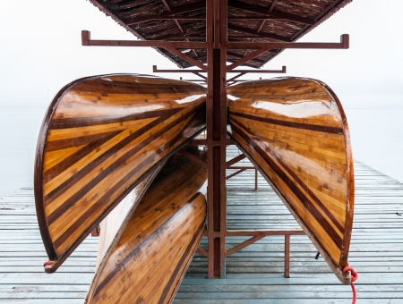 Wooden rowboat is hanging in the boat house in the early morning with fog