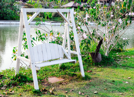 Wooden white swing on the grass of rural village  photo