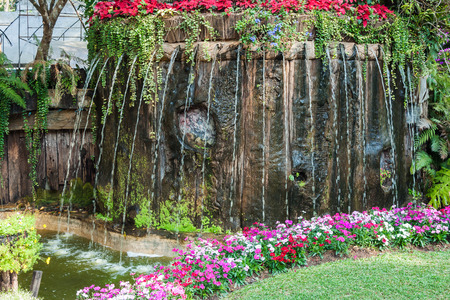 garish: Shower waterfall from the wooden island in flower garden