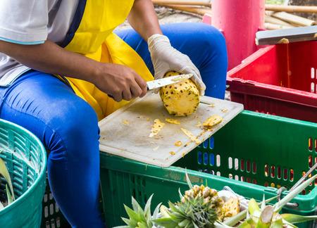 Seller is peeling pineapple in the fresh market photo
