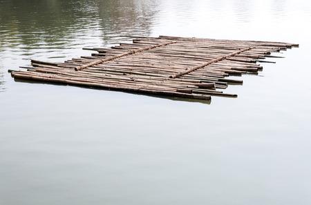 古い竹のいかだが朝の湖に浮かんでいます。