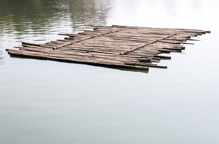 Old bamboo raft is floating on the lake in the morning. 版權商用圖片