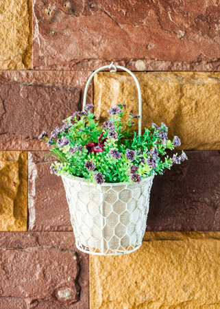 Artificial flower in the white basket. photo