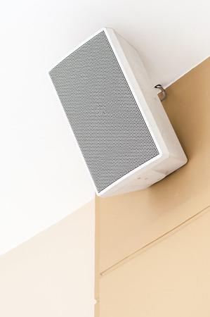 surround: White loudspeaker is hanging on the wall of shopping mall.