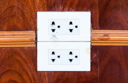 dirty room: Dirty white outlet on the wooden wall of living room. Stock Photo