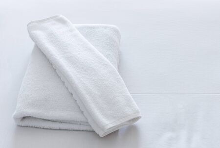 white towel: White towel set on the bed of hotel. Stock Photo