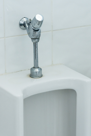 latrine: Chrome  flush handle  of the dirty urinals in the office restroom.