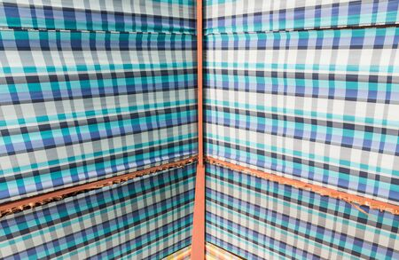 blue plaid: Metal frame roof with blue plaid fabric of the small cottage.