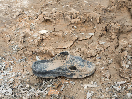 silt: Dirty rubber shoe with the dry mud in the construction site.