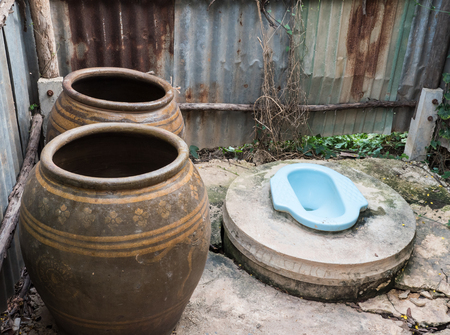 latrine: Dirty old toilet with the large jar in the countryside farm. Stock Photo