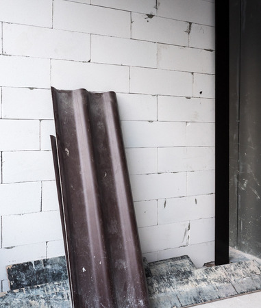 garage on house: Dark tile roof is laying on the brick wall for preparation to install on the construction house. Stock Photo