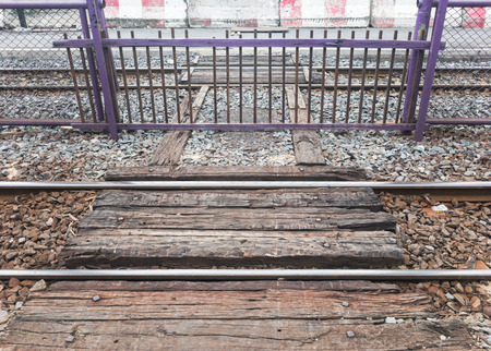 Small wooden fence in the metal fence row for protecting the people across the railway line When the train has arrived,uban train station in Thailand.