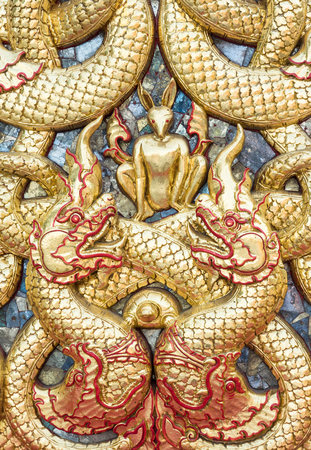 Golden dragon stucco with the small rabbit on the church wall in the Thai temple.(Public area not required Property Release) Stock Photo