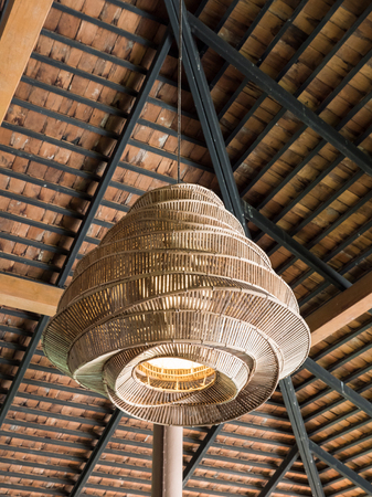 Electrical lamp with the bamboo weave is hanging on the metal frame of the Thai restaurant.