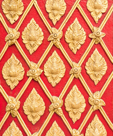Golden stucco pattern in the traditional Thail style on the red wall of the church,Thailand.(Public area not required Property Release)