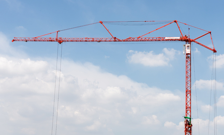 Red high crane with the worker in the metal frame for survey the lifting in the construction sit,copy space.