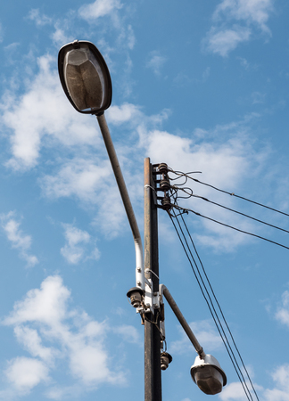 Electric pole from the rail with the twin lamp in the urban park.