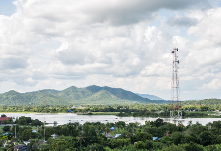 Telecommunication tower in the rural village near the large river, western of Thailand.