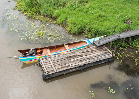 Long tail boat near the small wooden pontoon for service the traveler in the countryside of Thailand. 版權商用圖片 - 98352121