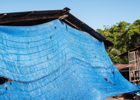Blue shading net is covering the terrace of the countryside house for protect from the hot temperature in Thailand.