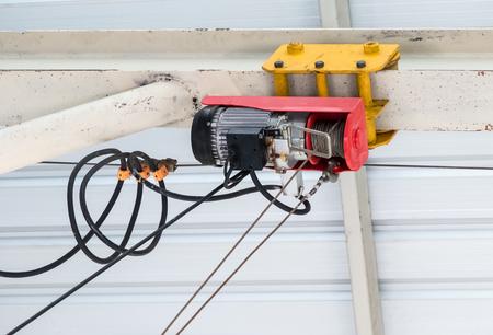 Un petit treuil électrique s'installe sur le cadre de plafond de l'usine. Banque d'images