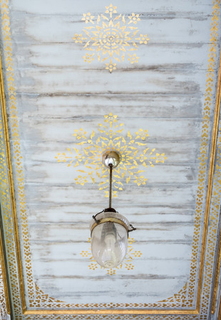 Old electrical lamp is hanging from the marble ceiling of the traditional Thai pavilion in the Thai temple.(copy space) 免版税图像
