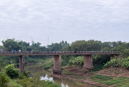 Long concrete bridge is over the curved river from the city area to the countryside area in the northeast of Thailand. Stock Photo