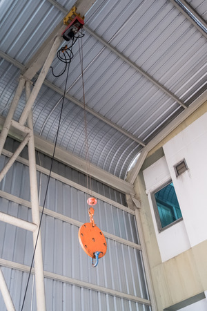 Small rope sling of the electric crane is hanging on the roof beam of the factory.