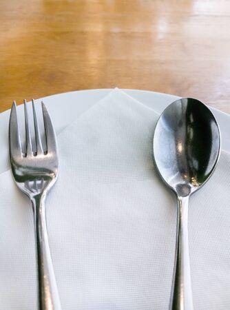Piatto bianco con il cucchiaio d'argento e la forchetta sul tavolo di legno nel ristorante.