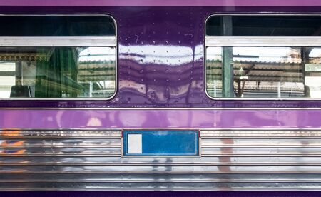 Side view of the stainless passenger car which park in the platform of the urban station. Stock Photo