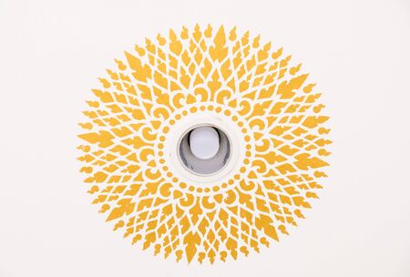 Circle pattern in the traditional Thai style around the led bulb which install on the ceiling of the Thai temple. Stock Photo