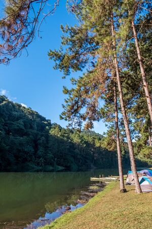 Camping field near the clear lake of the reservoir in the valley,Thai national park. 版權商用圖片